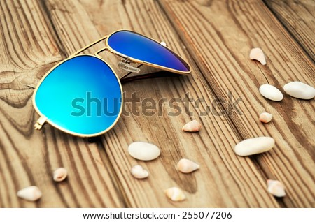 blue mirrored sunglasses and shells on the wooden background close up. horizontal - stock photo