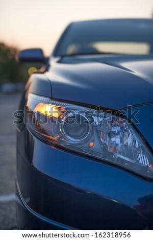 blue modern car closeup of headlight - stock photo
