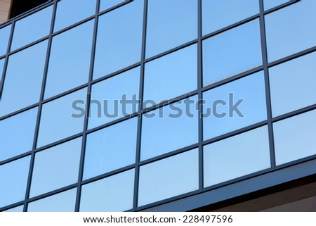 Blue modern facade of office building reflecting sky
