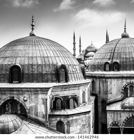 Blue Mosque or Sultan Ahmed Mosque viewed trough the window of Hagia Sophia, former Orthodox patriarchal basilica (church), later a mosque, and now a museum in Istanbul, Turkey. Black and white. - stock photo