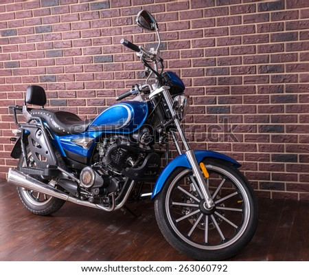 Blue motorbike parked on a wooden floor in front of a brick wall at an oblique angle with copyspace - stock photo