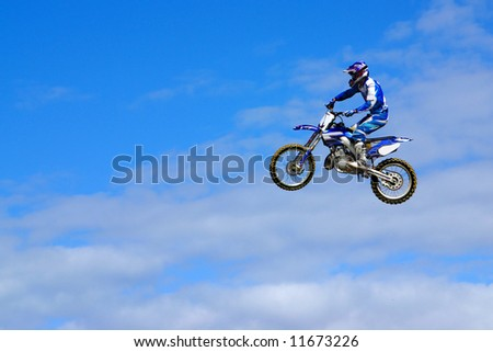Blue motorcycle and rider jumping in the sky