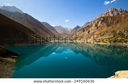 blue mountain lake surrounded by high peaks - stock photo