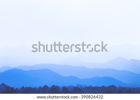 Blue mountains background in many layers covered by soft mist in the white sky - stock photo