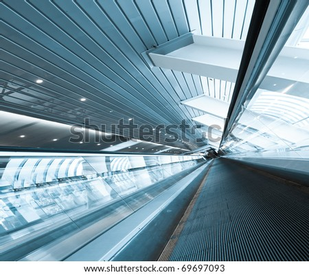 blue moving escalator in office center - stock photo