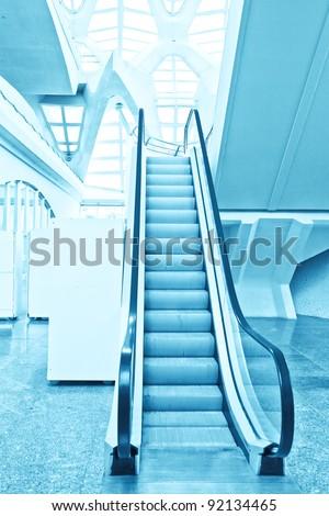 blue moving escalator inside shopping mall - stock photo