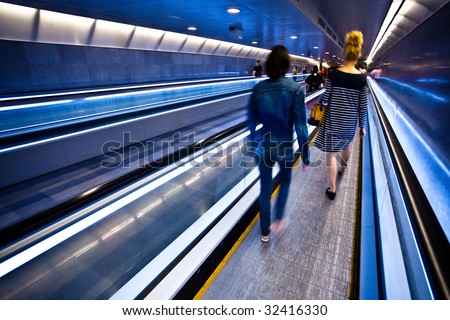 Blue moving escalator with people in Barcelona's subway - stock photo