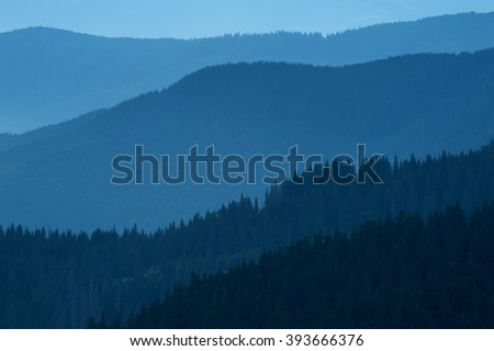 Blue nature background with mountain silhouettes and a pine tree forest. Smooth gradient from dark to light blue caused by the long-focus lens and twilight. Carpathian mountains, Marmorossy, Ukraine.
