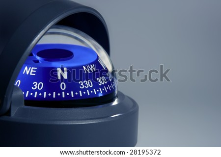 Blue nautical compass close up over gray background - stock photo