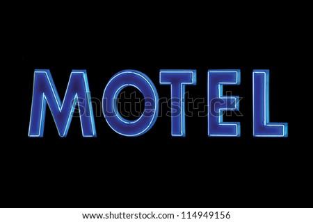 Blue Neon Motel sign lit up at night, isolated black large signage - stock photo