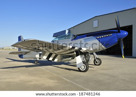 blue nose Mustang parked in front of a hangar - stock photo