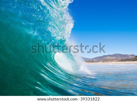 Blue Ocean Wave Breaks with Beach in Background - stock photo