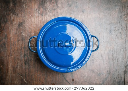 blue of cooking pot on wooden background - stock photo