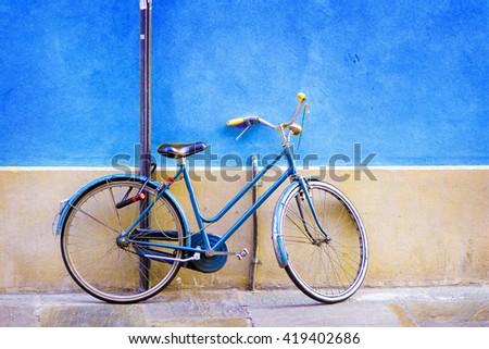 Blue old bicycle standing near blue wall. - stock photo