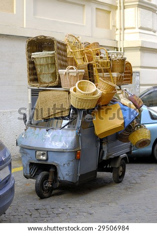 Blue over-burdened motor scooter in Rome - stock photo