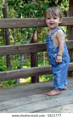 Blue Overalls on young boy standing by fence - stock photo