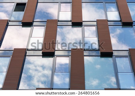 Blue overcast sky and clouds reflected in mirror windows of new modern office building with one open section - stock photo