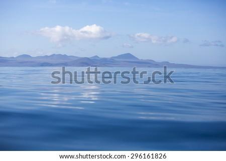 Blue Pacific Ocean and the coast of the isla Sant Cruz with a clear blue sky. Galapagos Islands. Ecuador 2015 - stock photo