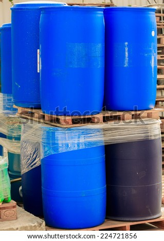 Blue packed barrels on paletts in a chemical plant - stock photo