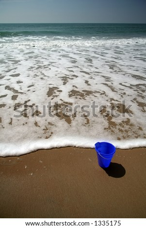 Blue pail in the sand on the beach with a wave approaching - stock photo