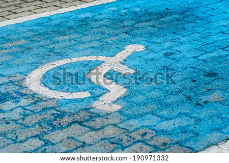 Blue painted parking space reserved for handicapped - stock photo