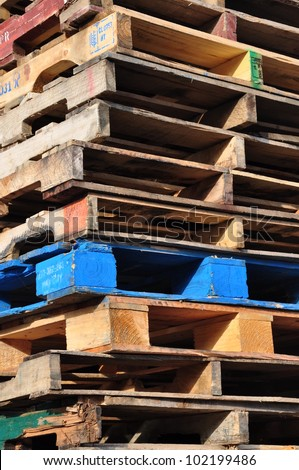 Blue pallet among stack of pallets - stock photo