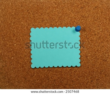 Blue paper with scalloped edges pinned to a corkboard. - stock photo