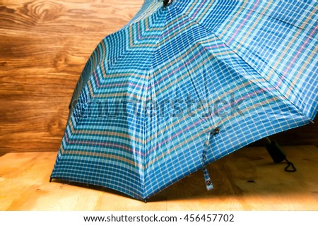 Blue patterned umbrella on wooden background - stock photo
