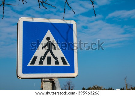 blue pedestrian crossing sign on the street