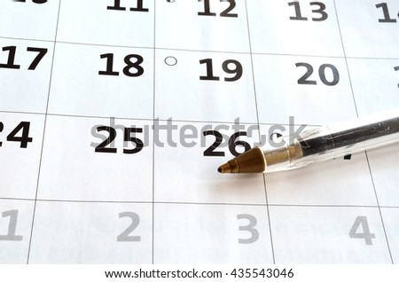 blue pen resting on a white blank calendar