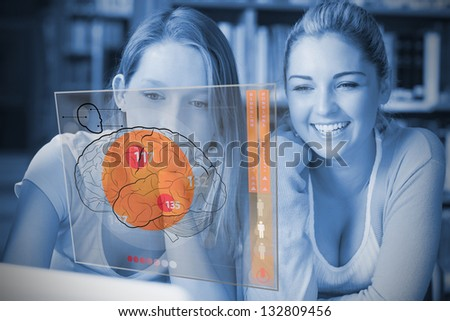 Blue picture of students studying with laptop and futuristic interface with brain diagram on it - stock photo