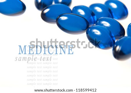 Blue pills isolated on white background with shallow depth of field - stock photo