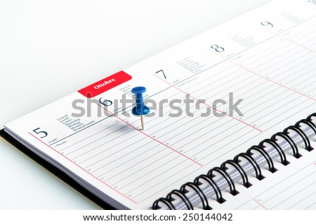 blue pin pointed on a spiral weekly agenda - stock photo