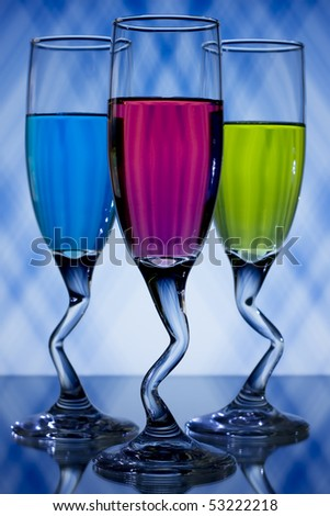 Blue, pink, and green, liqueur glasses on blue and white background