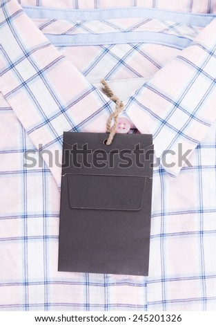 Blue pink plaid shirt background with price tag  - stock photo