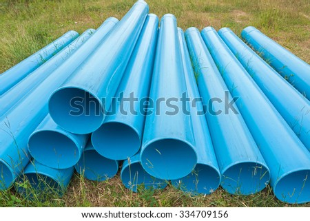Blue pipes for construction on filed - stock photo