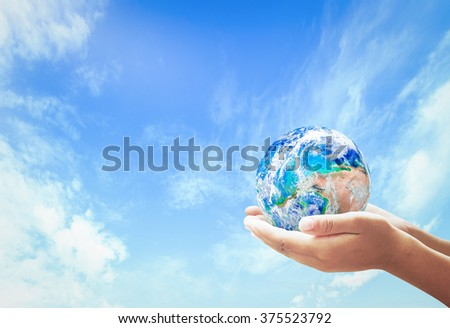 Blue planet in human hands on beautiful blue sky background. Elements of this image furnished by NASA. World Environment Day, Earth concept. - stock photo