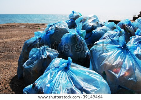 blue plastic garbage bags full of trash on the beach - stock photo