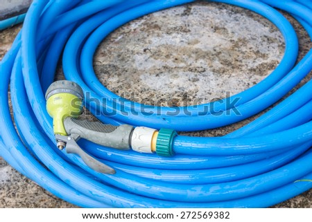 blue plastic garden hose pipe connected with spraying head - stock photo