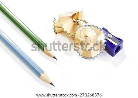 Blue plastic pencil sharpener with shavings and two pencils on white background - stock photo