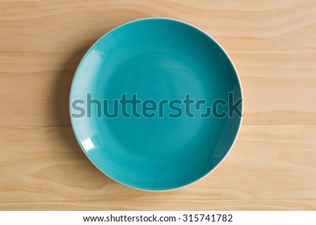 blue plate on wooden background - stock photo