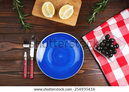Blue plate with fork and knife, on  wooden table with olives, lemon and rosemary - stock photo