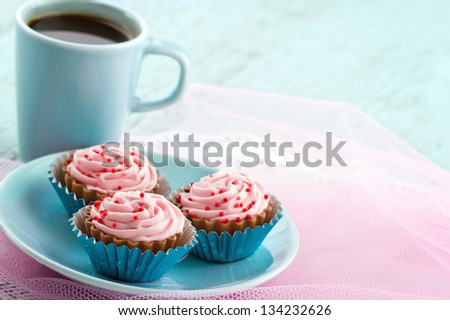 Blue plate with pink chocolate pralines and cup of coffee on pastel color background, with copy space - stock photo