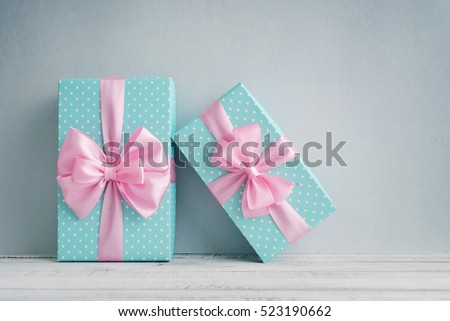 Blue polka dots gift boxes with pink ribbons on blue background