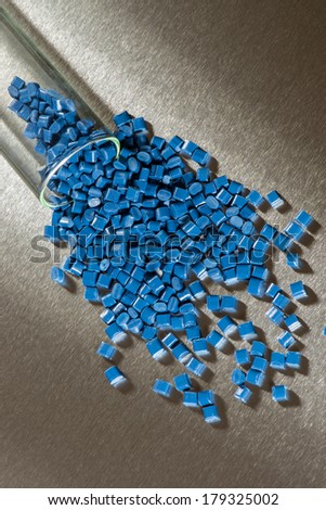 Blue polymer granulate on stainless steel sheet - stock photo