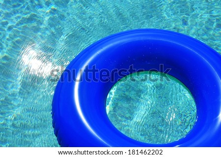 Blue pool float / ring in refreshing pool water - stock photo