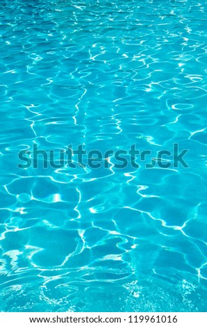 Blue pool water with sun reflections - stock photo