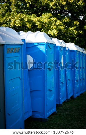 Blue portable toilets in a green field - stock photo