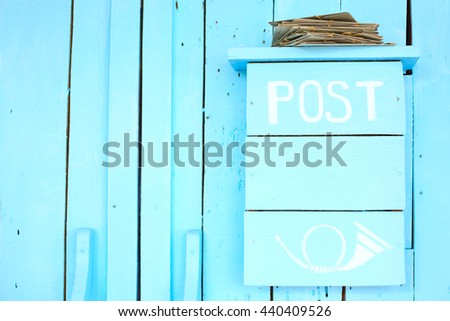 Blue post box on a wooden blue wall - stock photo