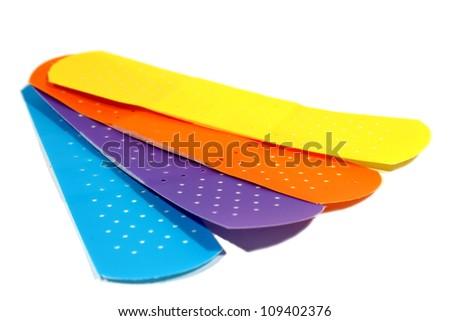 Blue, purple, orange, and yellow bandages sitting on an isolated background. - stock photo